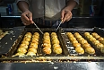 Chef cooking takoyaki, a ball-shaped Japanese snack made of a wheat flour-based batter and cooked in a special moulded pan. It is typically filled with minced or diced octopus, tempura scraps, pickled ginger, and green onion.